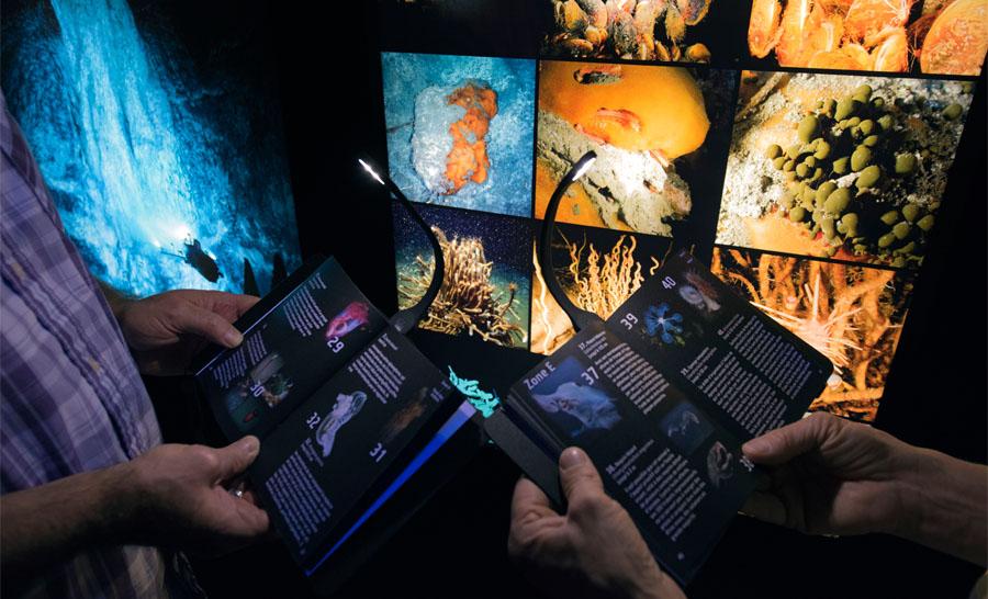Visiteurs utilisant les liseuses de légendes de l'exposition © museum Alain Germond