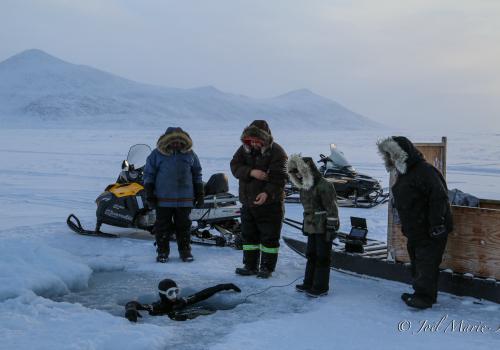 Sous l'œil étonné des Inuits, l'apnéiste Laurent Marie s'immerge sous la banquise. © Joël Marie