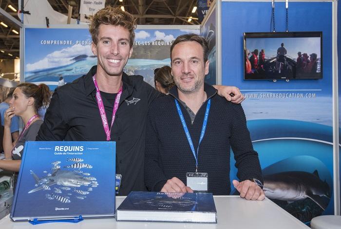 """Steven Surina et Greg Lecœur présentent leur livre """"Requins, guide de l'interaction"""" sur leur stand. © Dominique Barray"""