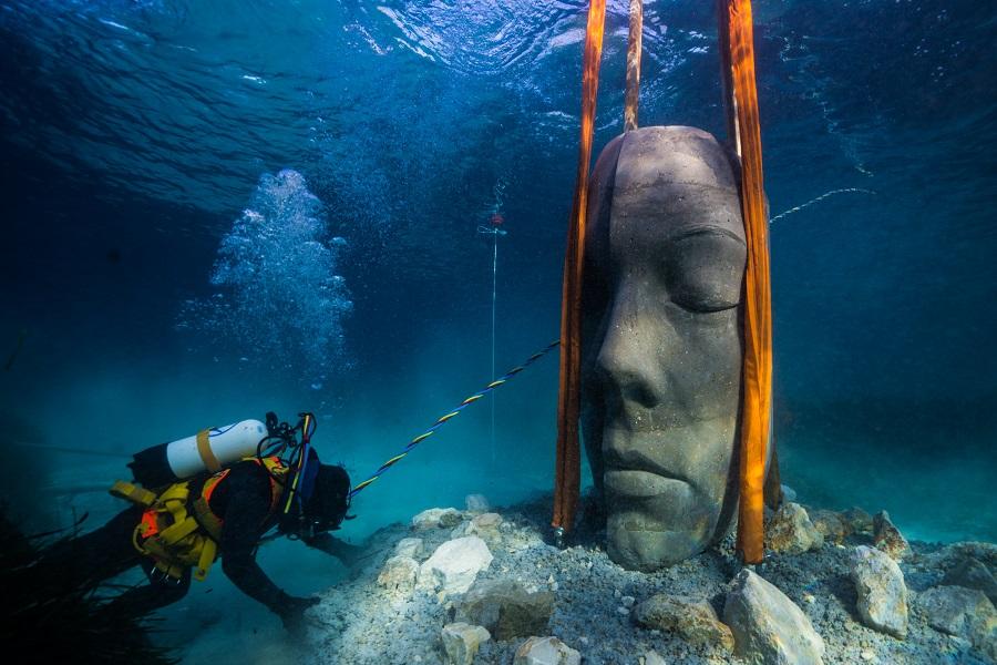 Installation d'une sculpture sur un fond de sable par un plongeur. © Jason deCaires Taylor