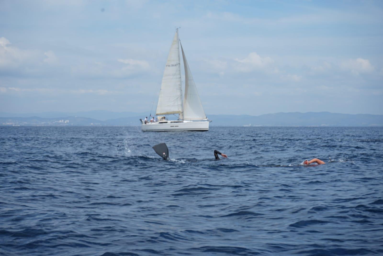 Andy Cabrera Avila encadré par des apnéistes de sécurité et suivi de près par divers embarcations. © Solène Chevreuil